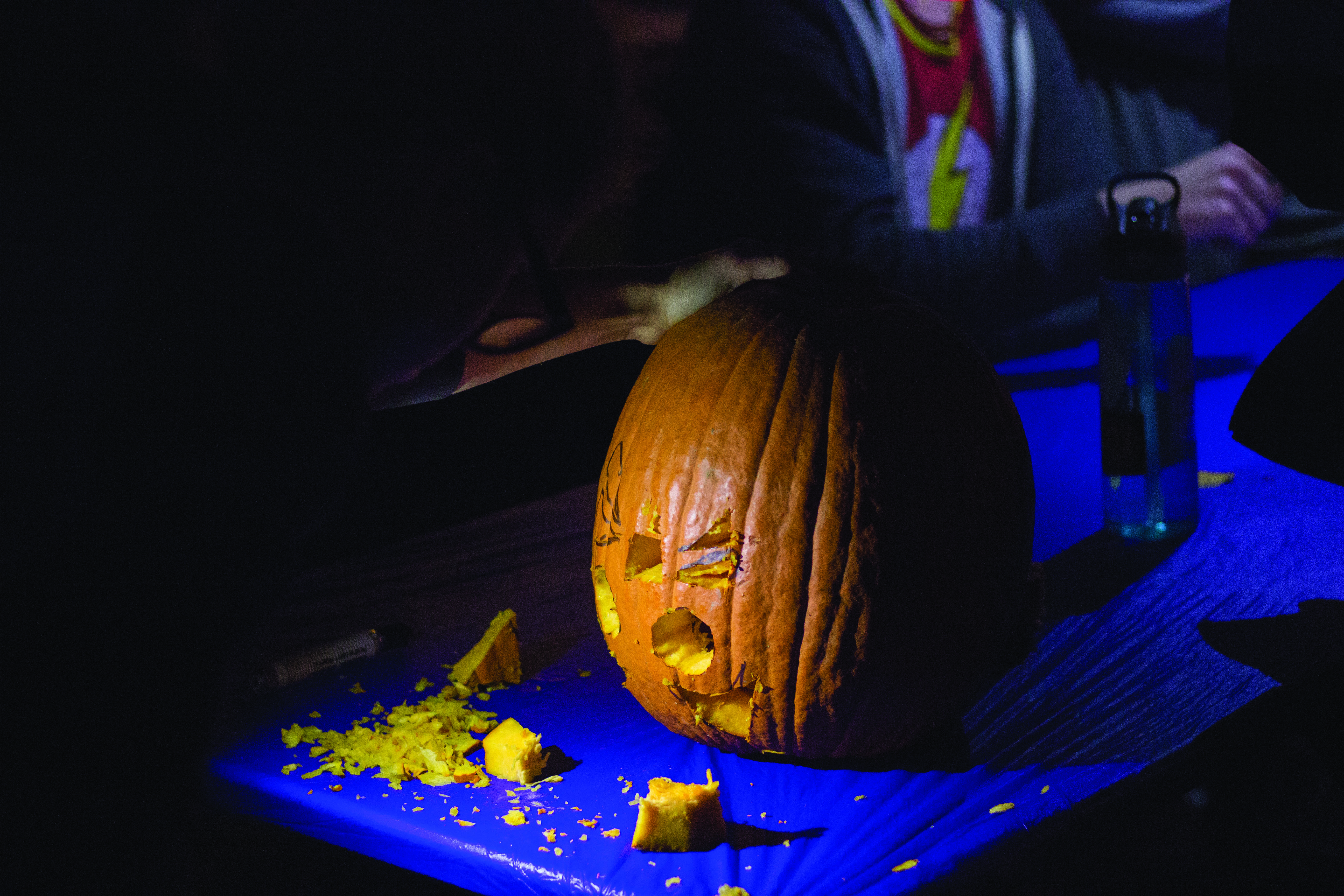 Some students opt to carve pumpkins outside instead of waiting in the lines for the movie.